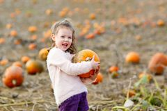 Adorable little kid girl having fun on pumpkin patch. Adorable little kid girl having fun on pumpkin patch farm. Traditional family festival with children Royalty Free Stock Image