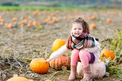 Adorable little kid girl having fun on pumpkin patch. Royalty Free Stock Photos