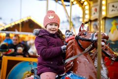 Adorable little kid girl riding on a merry go round carousel horse at Christmas funfair or market, outdoors. Happy child. Having fun on traditional family xmas royalty free stock images