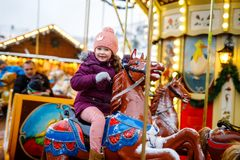 Adorable little kid girl riding on a merry go round carousel horse at Christmas funfair or market, outdoors. Happy child. Having fun on traditional family xmas stock images