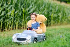 Adorable little kid girl sitting in big vintage old toy car and having fun with playing with big plush toy bear, Stock Photo