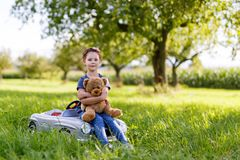 Adorable little kid girl sitting on big vintage old toy car and having fun with playing with big plush toy bear, Royalty Free Stock Image