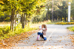 Adorable little kid girl and young woman in beautiful autumn forest. Daughter running to mother. Family portrait, fall Stock Photography