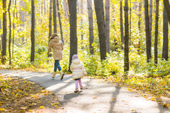 Adorable little kid girl and young woman in beautiful autumn forest. Daughter running to mother. Family portrait, fall Royalty Free Stock Photography