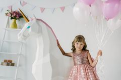 adorable little kid holding bunch of air balloons and standing with decorative stock photo