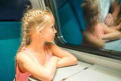 Adorable little kid looking out train window outside, while it moving. Royalty Free Stock Images
