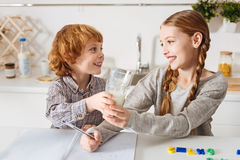 Adorable little kid offering his sister milk Royalty Free Stock Photos