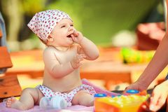 Cheerful baby sitting with toys. Adorable little kid sitting with toys on the bench and looking at mother stock photography