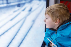 Adorable little kid traveling and looking out train window outsi. Adorable little kid looking out train window outside, while it moving. Going on vacations and Royalty Free Stock Image