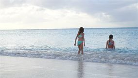 Adorable little girls relaxing on the beach. Adorable little kids at beach during summer vacation. Happy girls in shallow water playing together and swimming stock footage