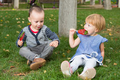 Adorable little kids with colorful lollipops Stock Photos