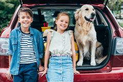 Adorable little kids with dog. In car trunk royalty free stock photo