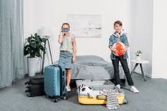 adorable little kids packing clothes for trip stock photo