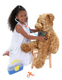 Adorable Little Playing Doctor To A Teddy Bear Over White stock photos