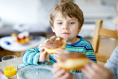 Adorable little preschool boy eating donut indoor. Adorable little school boy eating sweet donut indoor. Blond child in domestic kitchen or in school canteen Royalty Free Stock Photo