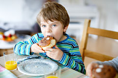 Adorable little preschool boy eating donut indoor. Adorable little school boy eating sweet donut indoor. Blond child in domestic kitchen or in school canteen Royalty Free Stock Photography