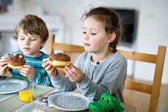 Adorable little preschool boy and girl eating sweet donut. Indoor. Child in domestic kitchen or in school canteen Cute kids and unhealthy sugared food Royalty Free Stock Image