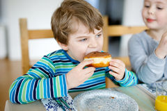 Adorable little preschool boy and girl eating sweet donut. Indoor. Child in domestic kitchen or in school canteen Cute kids and unhealthy sugared food Royalty Free Stock Images