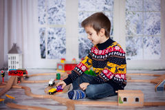 Adorable little preschool boy, playing with wooden trains and ra royalty free stock photo