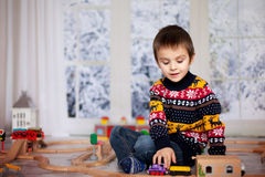 Adorable little preschool boy, playing with wooden trains and ra stock photography