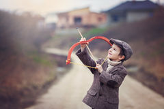 Adorable little preschool boy, shoot with bow and arrow at target in open air stock photo