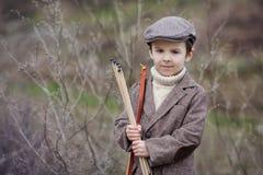 Adorable little preschool boy, shoot with bow and arrow at targe Stock Photos