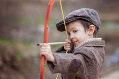 Adorable little preschool boy, shoot with bow and arrow at targe Stock Image