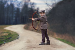 Adorable little preschool boy, shoot with bow and arrow at targe Stock Photo