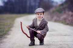 Adorable little preschool boy, shoot with bow and arrow at targe Royalty Free Stock Images