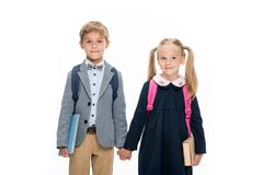 Pupils. Adorable little pupils holding hands isolated on white Royalty Free Stock Image