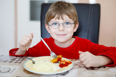 Adorable little school boy eating potato mash and chicken breast indoor. Blond child in domestic kitchen or in school canteen Cute kid and healthy food Stock Photos