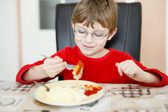 Adorable little school boy eating potato mash and chicken breast indoor. Blond child in domestic kitchen or in school canteen Cute kid and healthy food Royalty Free Stock Photos