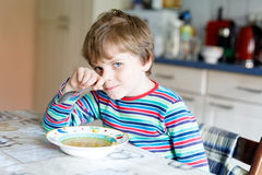 Adorable little school boy eating vegetable soup indoor. Blond child in domestic kitchen or in school canteen. Cute kid and healthy food, organic vegan soup Stock Photography