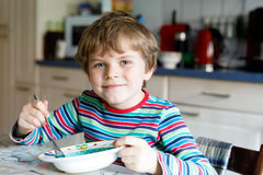 Adorable little school boy eating vegetable soup indoor. Blond child in domestic kitchen or in school canteen. Cute kid and healthy food, organic vegan soup Stock Image
