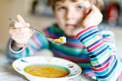 Adorable little school boy eating vegetable soup indoor. Blond child in domestic kitchen or in school canteen. Cute kid and healthy food, organic vegan soup Royalty Free Stock Photography