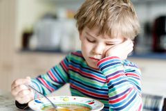 Adorable little school boy eating vegetable soup indoor. Blond child in domestic kitchen or in school canteen. Cute kid and healthy food, organic vegan soup Stock Photo