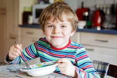 Adorable little school boy eating vegetable soup indoor. Blond child in domestic kitchen or in school canteen. Cute kid and healthy food, organic vegan soup Royalty Free Stock Photo