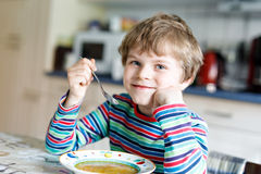 Adorable little school boy eating vegetable soup indoor. Blond child in domestic kitchen or in school canteen. Cute kid and healthy food, organic vegan soup Royalty Free Stock Photos