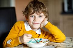 Adorable little school boy eating vegetable soup indoor. Blond child in domestic kitchen or in school canteen. Cute kid and healthy food, organic vegan soup Royalty Free Stock Images