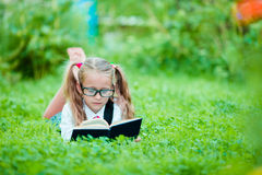 Adorable little school girl with book outdoor. Back to school Royalty Free Stock Photography