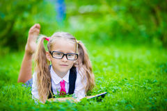 Adorable little school girl with book outdoor Stock Photography