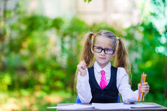 Adorable little school girl at desk with notes and Royalty Free Stock Images