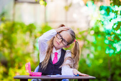 Adorable little school girl at desk with notes and Royalty Free Stock Photography