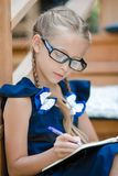 Adorable little school girl with notes and pencils outdoor. Back to school. Royalty Free Stock Photography