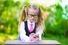 Adorable little school girl at a table with notes Royalty Free Stock Photo