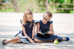 Adorable little school girls with notes and pencils outdoor. Back to school. Stock Photo