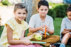 adorable little schoolgirl with apple and book sitting on grass royalty free stock image