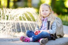 Adorable little schoolgirl in a city park Stock Photography