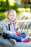 Adorable little schoolgirl in a city park on bright autumn day Stock Images