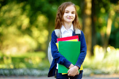 Adorable little schoolgirl in a city park on bright autumn day Royalty Free Stock Image